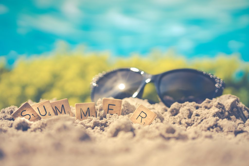 """Sunglasses sitting on sand with wood blocks that have letters that spell """"summer""""."""